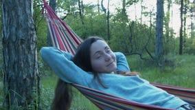 Een lachend meisje schommelt in een hangmat Portret van een rustende jonge vrouw buiten de stad Gelukkige vrije tijd in aard stock video