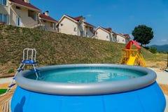 Een ladder in een klein bassin in de vorm van een kom met duidelijk blauw water Status naast de speelplaats en de vakantie stock afbeeldingen