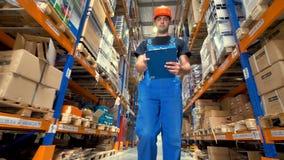 Een lage mening over een arbeider het inspecteren pakhuislading stock video