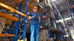 Een lage mening over een pakhuissupervisor die gedetailleerde inventaris nemen stock footage