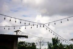 Een lampbol op de draden, op achtergrond van een hemel alvorens te regenen Stock Fotografie