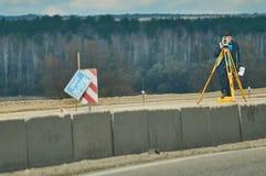 Een land-landmeter terwijl het werken aan een strook van weg in het Kaluga-gebied (Rusland) Royalty-vrije Stock Afbeelding