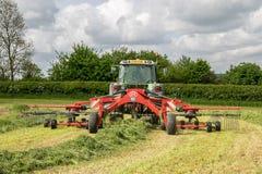 Een landbouwbedrijf fendt tractor met rota hark klaar om kuilvoeder te maken Stock Foto's