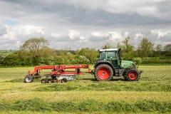 Een landbouwbedrijf fendt tractor met rota hark klaar om kuilvoeder te maken Royalty-vrije Stock Afbeelding