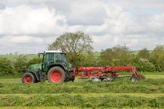 Een landbouwbedrijf fendt tractor met rota hark klaar om kuilvoeder te maken Stock Afbeeldingen