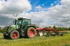 Een landbouwbedrijftractor met rota hark klaar om kuilvoeder te maken Royalty-vrije Stock Foto
