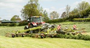 Een landbouwbedrijftractor met rota hark klaar om kuilvoeder te maken Royalty-vrije Stock Foto's