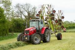 Een landbouwbedrijftractor met rota hark klaar om kuilvoeder te maken Stock Fotografie