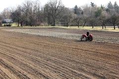Een landbouwer ploegt het gebied in de lente Royalty-vrije Stock Foto's