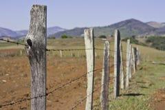 Een landbouwprikkeldraadomheining stock foto