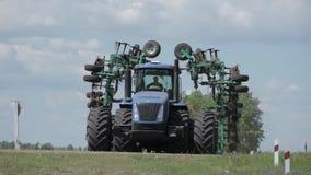 Een landbouwtrekker, die een gebied ploegen alvorens te zaaien, stock videobeelden