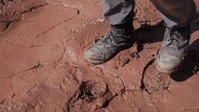 Een landloper in vuile en gescheurde kleren loopt in de woestijn met een verband op zijn mond stock video