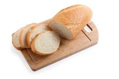 Een lang brood dat op een scherpe raad wordt gesneden Stock Fotografie