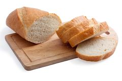Een lang brood dat op een scherpe raad wordt gesneden Stock Foto's