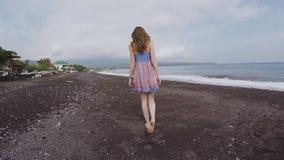 Een lang meisje loopt langs een zwart strand uit vulkanisch zand in Bali stock video
