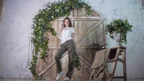 Een lang model stelt actief en danst met een glimlach tegen de achtergrond van een houten photozone stock foto's