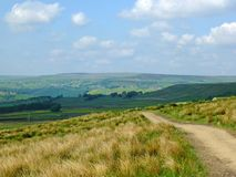 Een lang voetpad die bergaf in stoodley lopen legt in Yorkshire met gebieden en landbouwbedrijven in de afstand met pennine heuve stock foto