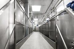 Een lange doorgang tussen twee rijen van reservoirs Opslag van voedselvloeistoffen royalty-vrije stock afbeeldingen