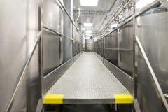 Een lange doorgang tussen twee rijen van reservoirs Opslag van voedselvloeistoffen royalty-vrije stock foto's