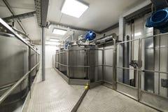 Een lange doorgang tussen twee rijen van reservoirs Opslag van voedselvloeistoffen royalty-vrije stock afbeelding