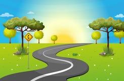 Een lange en windende weg bij het bos Stock Afbeeldingen