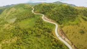 Een lange en windende weg die door groene heuvels overgaan Busuangaeiland Coron Lucht Mening filippijnen stock fotografie