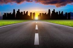 Een lange rechte weg en cityscape bij zonsondergang royalty-vrije stock fotografie