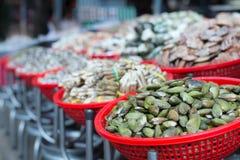 Een lange rij van mandenhoogtepunt van mosselen, tweekleppige schelpdieren, en een groot assortiment van schaaldieren stock foto's