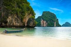 Een lange staartboot door het strand in Thailand stock foto's
