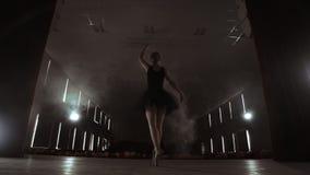 Een langzaam dansende ballerina voor vleklichten Verscheidene schijnwerpers tonen een dansende ballerina in een donker stadium in stock videobeelden