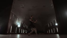 Een langzaam dansende ballerina voor vleklichten Verscheidene schijnwerpers tonen een dansende ballerina in een donker stadium in stock video