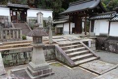 Een lantaarn en een steen steles verfraaien de binnenplaats van een tempel (Japan) Stock Foto's