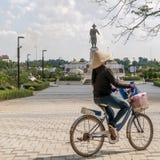 Een Laotiaanse vrouw berijdt een fiets in het Chao Anouvong-park met het grote standbeeld van Koning Chao Anouvong op de achtergr royalty-vrije stock afbeeldingen