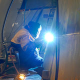 Een lasser die bij scheepswerf werken stock foto