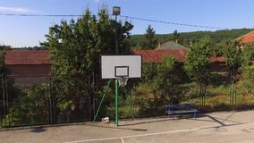 Een leeg basketbalhof die rond de mand vliegen stock footage
