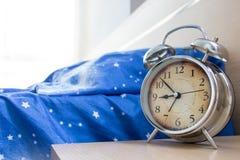 Een leeg bed met een wekker stock fotografie