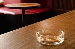 Een leeg glasasbakje op een lijst in een koffie Royalty-vrije Stock Afbeeldingen