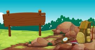 Een leeg houten uithangbord dichtbij de rotsen met een zak stock illustratie