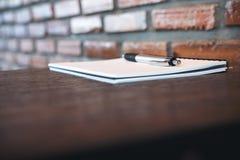 Een leeg wit notitieboekje en een zilveren kleurenpen op houten lijst met bakstenen muur Stock Foto's