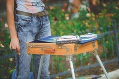 Een leerling van een kunstacademie trekt in een park sketchbox met verven, close-up stock afbeeldingen