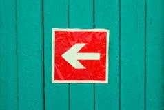 Een leftwards witte die pijl op de muur van houten panelen omvat met groene verf wordt gemaakt Stock Fotografie