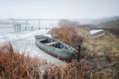 Een lege boot ligt op de rivierbank in de winter royalty-vrije stock afbeeldingen