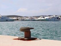 Een lege meerpaal op de jachthaven in de jachthaven tegen de achtergrond van jachten in de zonnige dag Oranje verlichting Gebrek  royalty-vrije stock foto
