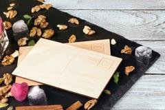 Een lege prentbriefkaar op een houten achtergrond Leuke ijsharten, kaneel, noten en een nota Uitnodiging, vieringsconcept De ruim Stock Foto's