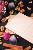 Een lege prentbriefkaar op een zwarte achtergrond Leuke ijsharten, kaneel, noten en een nota Uitnodiging, vieringsconcept De ruim Stock Afbeelding