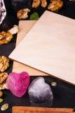Een lege prentbriefkaar op een zwarte achtergrond Leuke ijsharten, kaneel, noten en een nota Uitnodiging, vieringsconcept De ruim Stock Fotografie
