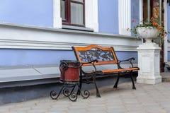 Een lege smeedijzerbank met houten panelen en vuilnisbak op de achtergrond van blauwe muur Stock Fotografie