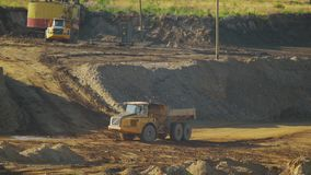 Een lege vrachtwagenritten van de mijnbouwstortplaats door een zandige carrière stock videobeelden