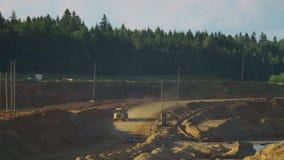 Een lege vrachtwagenritten van de mijnbouwstortplaats langs de helling van de heuvel stock footage