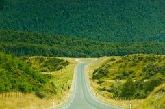 Een lege weg die in de heuvels gaat Stock Foto